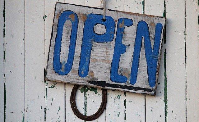 modrý nápis open na bílé ceduli na dveřích